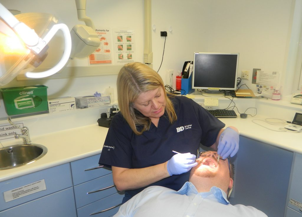 Brighter Dental dentist in clinic performing checkup on patient